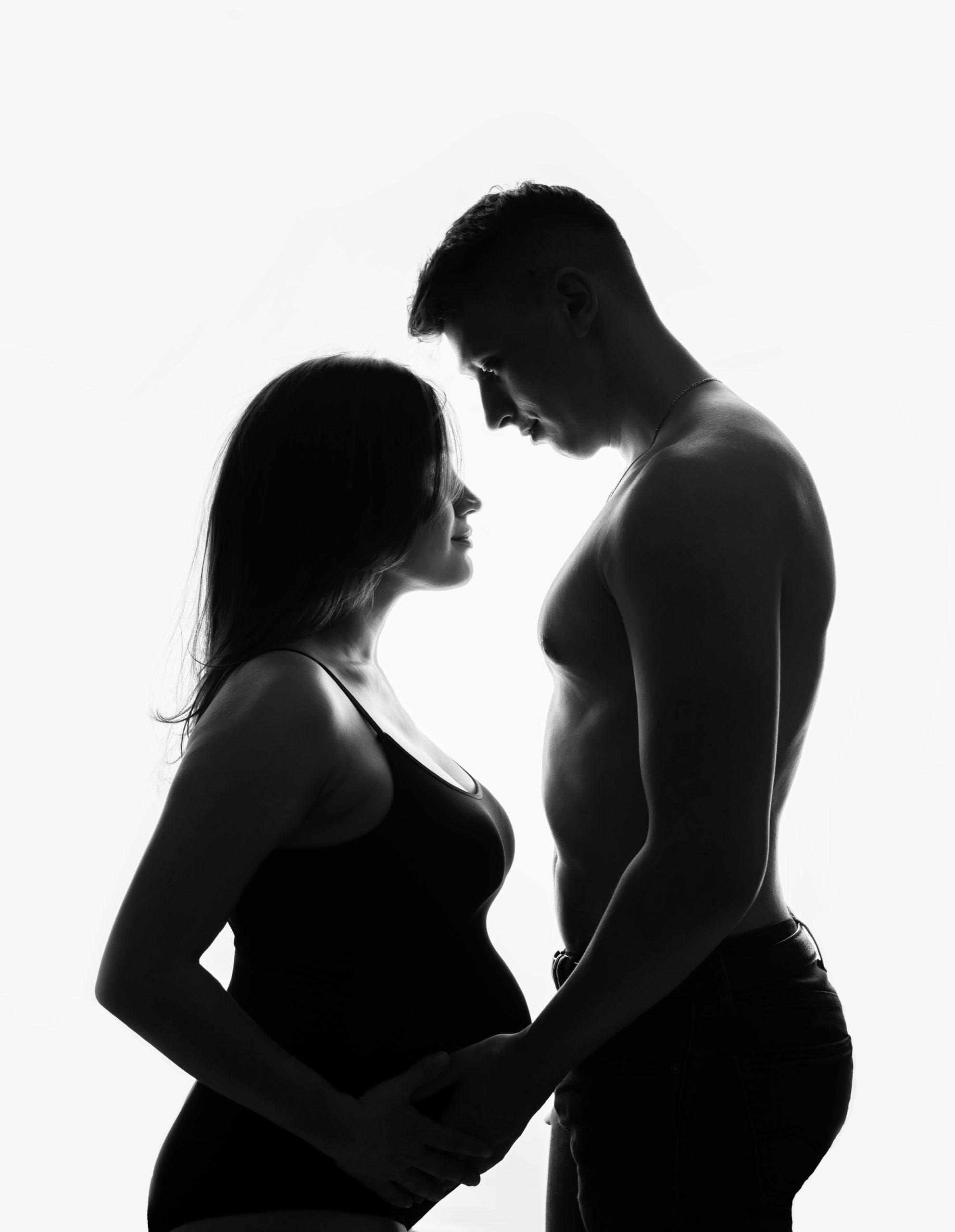 Photo grossesse de silhouette de belle femme enceinte avec future papa réalisée pendent une séance grossesse stylisée avec maquillage et coiffure professionnelles